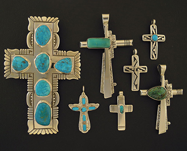 6 cross pendants organized from largest to smallest.