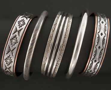 An image of a five silver and copper bracelets.